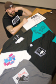 Ugly duckling Jesse Wallace, cofounder of Feo, displays several T-shirt designs produced by the growing company. Feo's shirts are available at Midwest Skate in West Ridge Mall and at The Looking Glass, located at 21st and Washburn Ave.