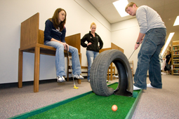 Freeze gopher! Zach Lee, student at Kansas State University, burns some rubber at CaddyStacks Saturday in Mabee Library. Accompanying him on the links were Robin Grenier (left) and Samantha Grief.