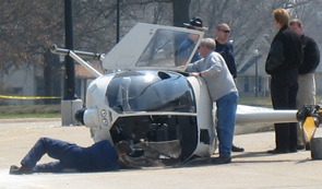 Crash and burn Members of the Topeka Police Department and Kansas State Highway Patrol examine the Robinson R-44 helicopter that made a crash-landing April 4 in the parking lot north of Stoffer Science Hall.
