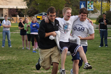 Will Falk and Brady Rothrock carry Richard Budden in the Sheet Race during the Greek Olympics last week.