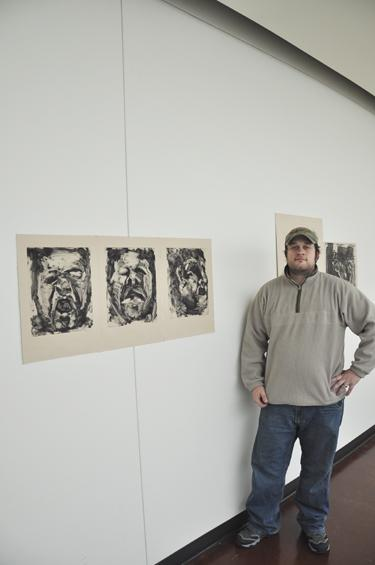 Senior show Casey Melton poses with his handiwork. Melton's art was showcased in his senior art exhibit, and displayed the culmination of his work at Washburn University.