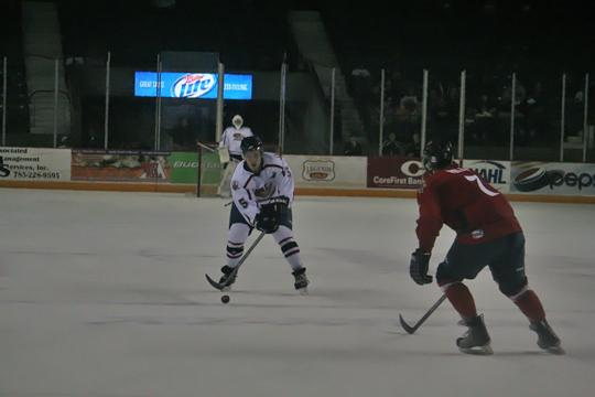 Jacob Poe holds on the puck in along the blue line Saturday night. Poe scored a rare goal and helped propel Topeka to a 5-4 victory