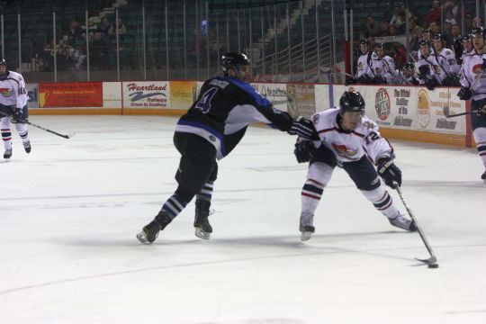 A hold up Ryan White attempts to move through the offensive zone on Friday night while fighting through a hold by Russell Finch. White and the RoadRunners couldn't mount a comeback late in the game as they fell 3-2.