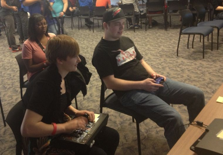 Avauni Morris, Destany Meeks and Tyler Hazelton play a round of Street Fighter X Tekken. Mini-cake Meltdown was open to Washburn students cush as Hazelton, as well as members of the community like Meeks and Morris.