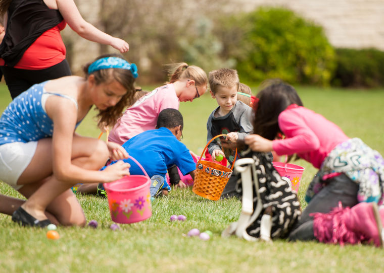 Gathering eggs in baskets at the Washburn Easter Egg Hunt.​