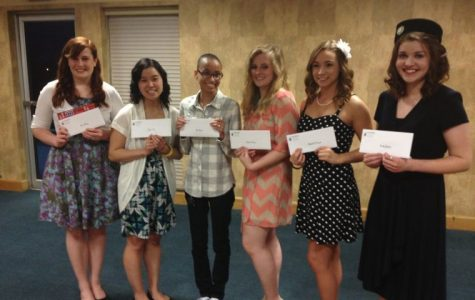 Student posing with scholarships they were awarded with during the mass media banquet.