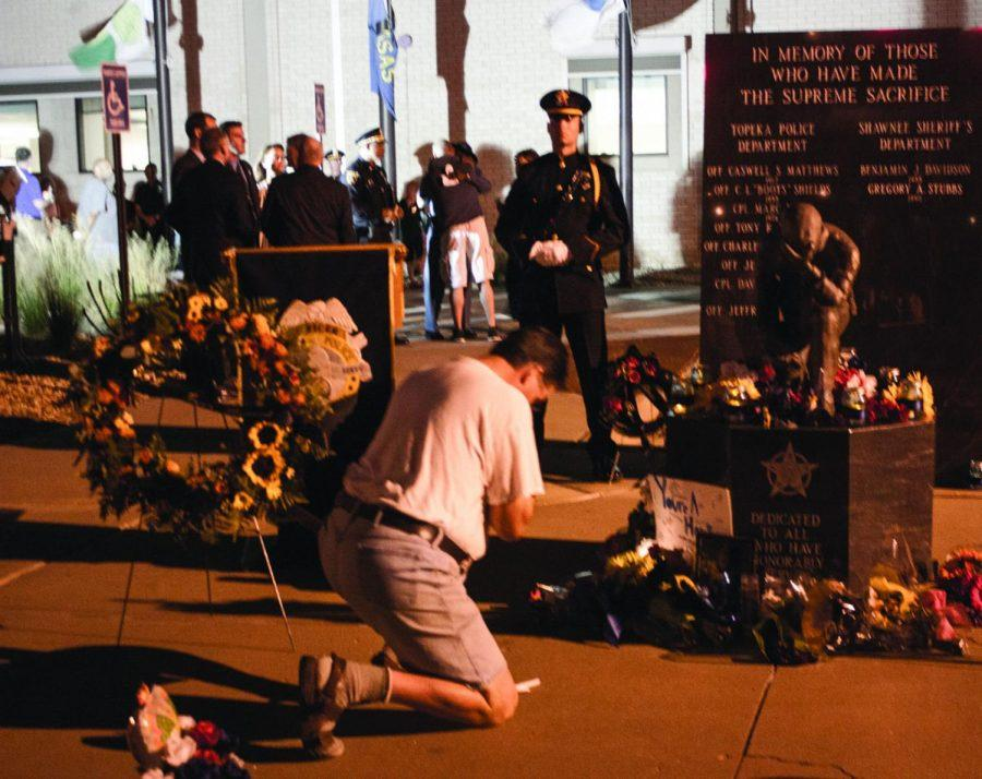 Honoring a Fallen Hero: Pierre Sutphin, Topeka, kneeled in front of the Fallen Officer's Memorial Monday night during the candlelight vigil for Cpl. Jason Harwood. Local leaders and law enforcement officials urged Topekans to remain united and strong in the wake of this weekend's tragedy.
