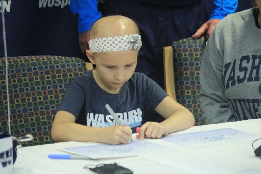 7 year-old Karis Selk signs letters of intent to play at Washburn University. Karis was diagnosed with brain cancer in 2012 but is now in remission. She has been adopted by the volleyball and women's basketball team as an honorary member.