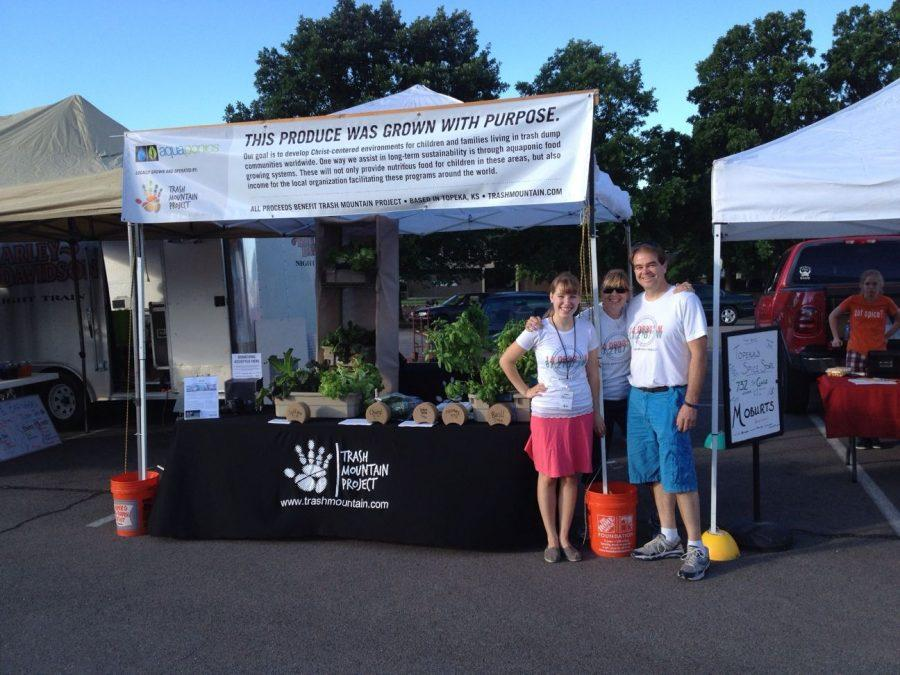 [left to right] Mollyanne Gibson with Chris and Carol Mammoliti, who run local non-profit organization Trash Mountain Project, pose in front of the TPM booth at Topeka's farmer's market.
