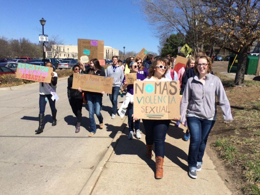 During the March to End Rape Culture, students pass through Lot 9 carrying decorated cardboard signs. The intention of the march was to raise awareness about rape culture in the United States.
