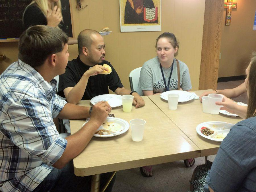 The Catholic Campus Center's new chaplain, Jonathan Dizon, joins students for dinner at Sunday's kick-off barbecue.