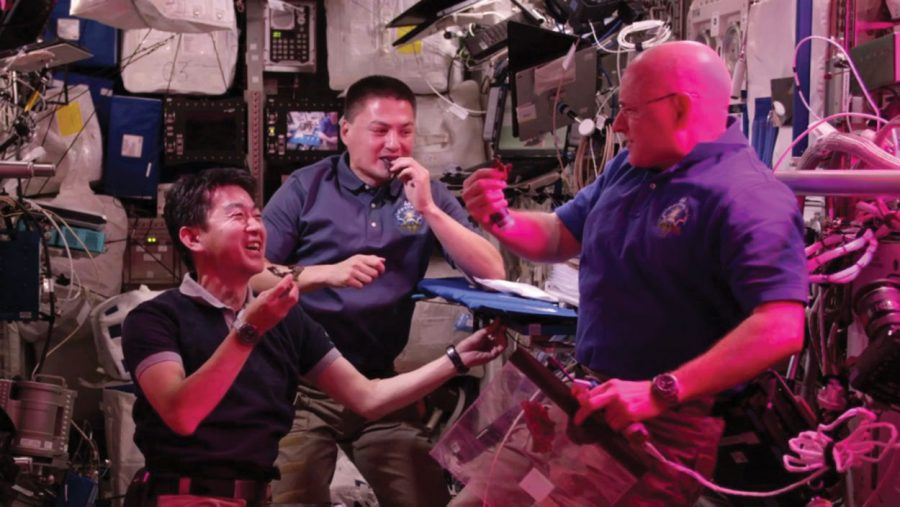 Astronaut Scott Kelly, right, takes his first bite of space-grown Red Romaine lettuce.