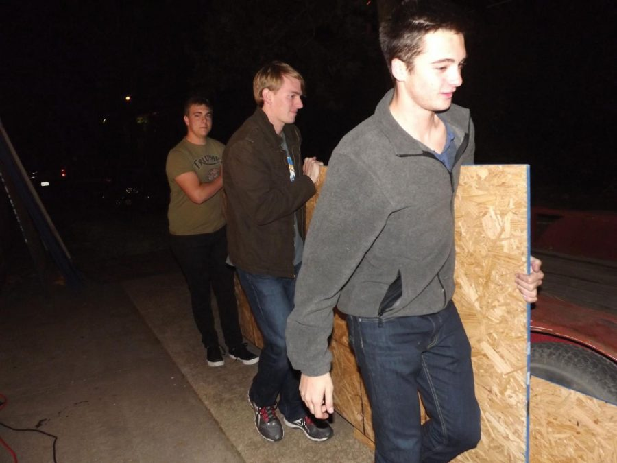 Skyler Urban, Trevor Bollinger and Ian McClain lifting a plank for the homecoming float.