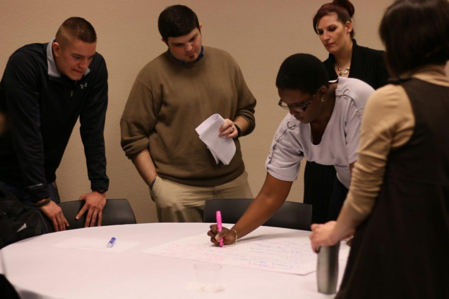 A group of students discusses and writes down their ideas for how to make diversity at Washburn more inclusive of minority student experiences.