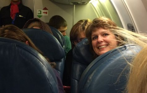 Faculty leader, Sharon Sullivan peeks around the airplane seats as our plane takes off from Kansas City International Airport.