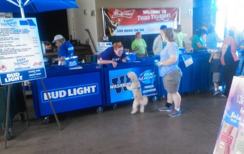 A small dog steps up to greet a woman at a booth at Third Thursday.