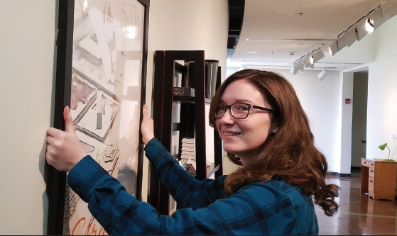 Hanging in There: Coultis hangs a poster with the name and logo of the fictional company she created for an art project. Student's don't just create the art for their show, they must also design how their artwork will be placed throughout the gallery before the show begins.