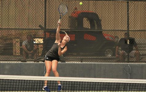 Tennis: Logan Morrissey jumps for the ball during her April 12 doubles match against Baker University.