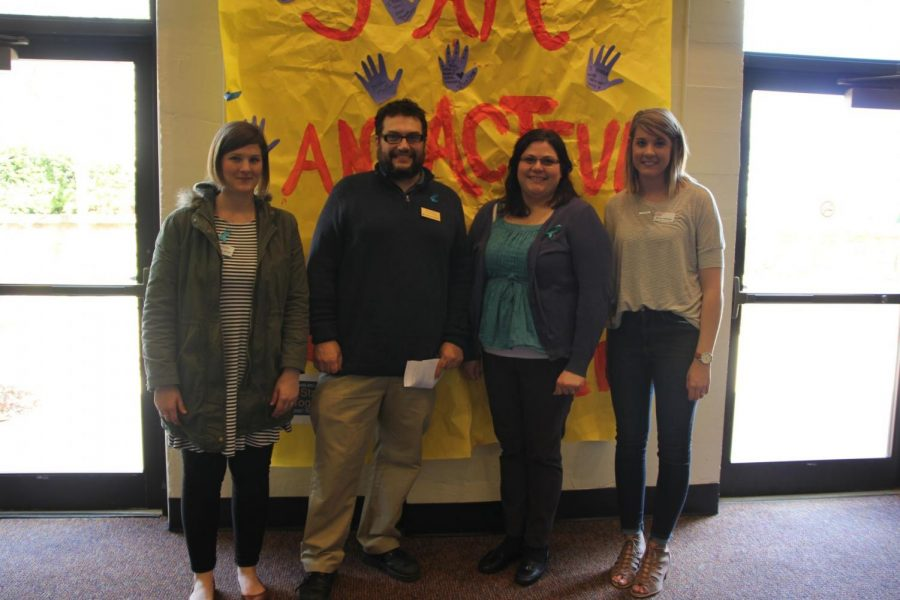 Standing Together: Molly Steffes-Herman, Washburn Victim Advocate; Dennis Etzel Jr., Department of English; Shelley Bearman, Project Coordinator of Sexual Assault Education and Prevention; and Emily Stermel, Public Education Coordinator at the YWCA Center for Safety and Empowerment standing in front of a poster with the words