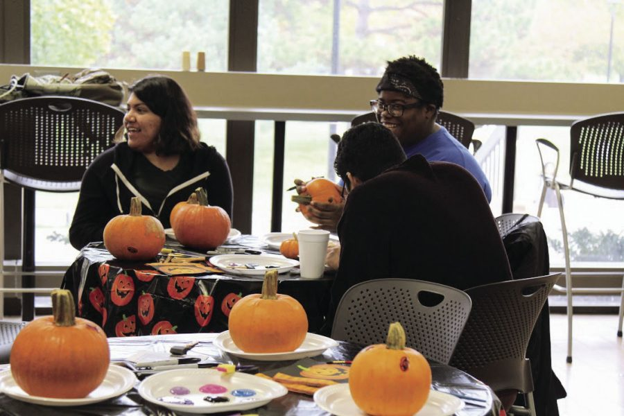 Sitting together: Students paint and talk during CAB's DIY series. The first day was painting pumpkins, the second day was string art and the third day will be making hot chocolate jars.