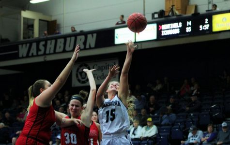 Under pressure: junior, Alexis McAfee shoots with defensive pressure against an MIAA conference opponent in Lee Arena.