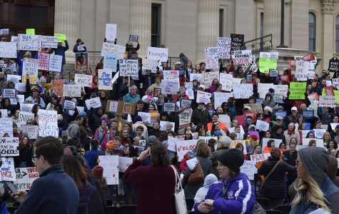 Stepping up: The crowd gathered on the steps of the state house at the end of the rally and held their signs for all to see.