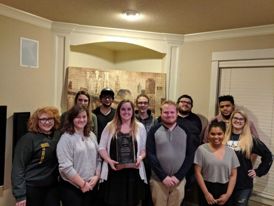 Washburn Debate stands together with their national championship trophy. The team brought home its fifth championship since 2010.