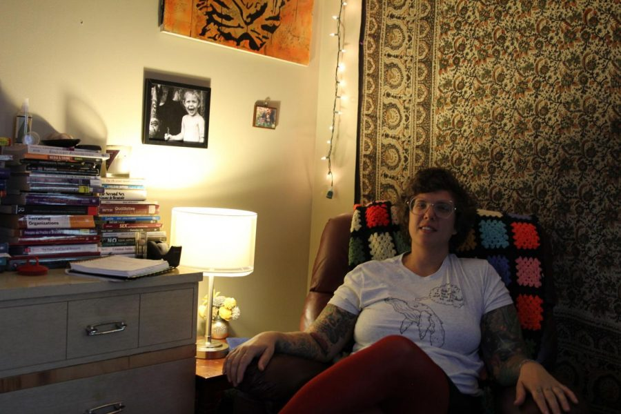 Chilling Comfortably: Erin Grant sits on her recliner wearing her existential shirt of a whale crying,
