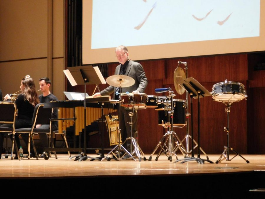"Music of Noah's Ark: Professor Tom Morgan, director of percussion studies, performs his piece ""Noah"" with the Washburn Faculty Woodwind Quintet while flashing artwork by Rita Blitt on the projector. Morgan worked on this piece for many months."
