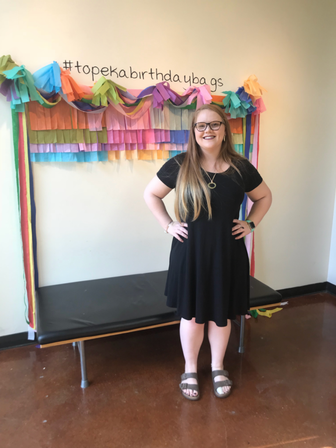 Alexandria Henderson posed in front of the sign for her creation of Topeka Birthday Bags. This project will officially debut on Thursday Oct. 11.