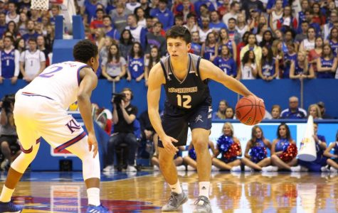CROSSOVER:Sophomore Tyler Geiman looks to cross up the KU defender in the exhibition game at Allen Fieldhouse earlier this year. Geiman broke the Blue Valley High School assist record during his time in high school.