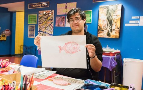 Fish printing: Errick Guzman is a  sophomore history major with an emphasis in education. He helped people to make Gyotaku in the Art Lab.