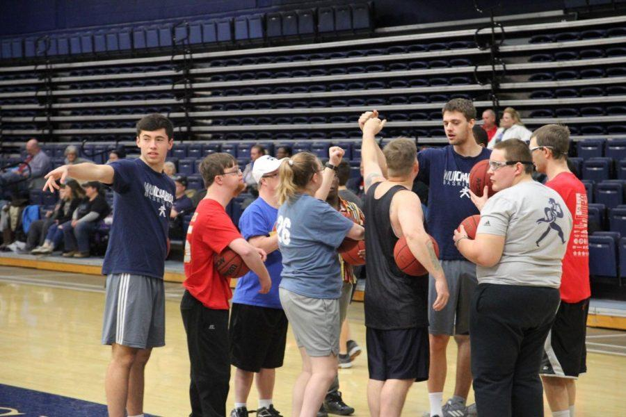 Tyler Geiman (left) and David Salach (middle of group) gather their group together for a quick pep talk before they send them to their next station. Nearly 50 athletes participated in the annual Special Olympics basketball clinic.