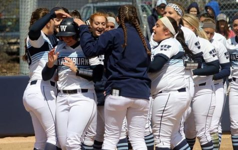 We are a team: The softball team surrounds home plate to celebrate senior Savannah Moore after she hit a home run. Moore was an all-MIAA third baseman.