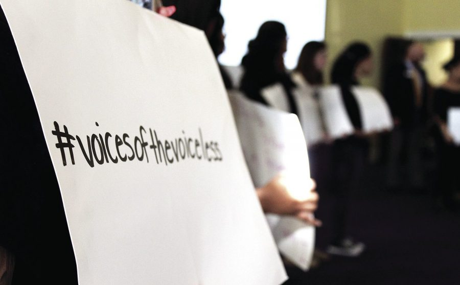Speaking for those who cant:A group of about 30 students holding signs entered the discussion on March 18 in Bradbury Thompson Alumni Center. On the front of the signs, students share their experiences of discrimination, and on the back, each sign reads #voicesofthevoiceless.