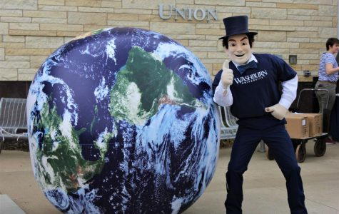 Thumbs up: The Ichabod mascot poses in front of a giant Earth ball adorning the Memorial Union Patio for Earth Day. The ball served as a focal point for the celebration.