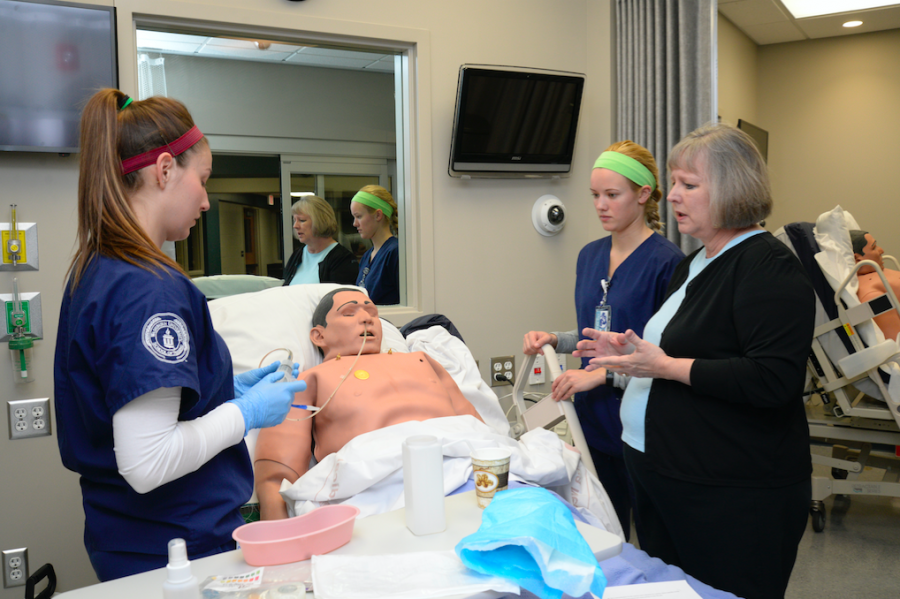 Patient instruction: Jane Carpenter guides Washburn nursing students on nasogastric tube insertion during a simulation.