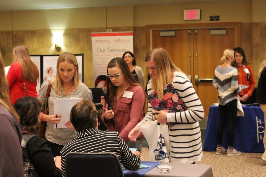 An exciting opportunity: Health care students crowd a booth at the career fair. The fair was held Wednesday, Oct. 16.