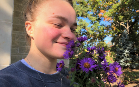 Inhale and exhale: Sophomore Kaylee Schweer stopped to smell some flowers on campus in between classes. Certain scents have been found to conjure memories and alleviate stress.