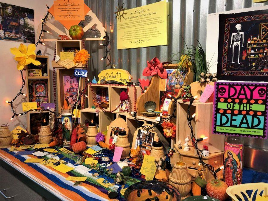 Community+Ofrenda%3A+A+yellow+sign+above+the+ofrenda+calls+it+a+place+to+%22display+favorite+foods+and+objects+that+the+departed+would+appreciate.%22+Community+members+were+invited+to+add+their+loved+ones%27+names+to+the+ofrenda.