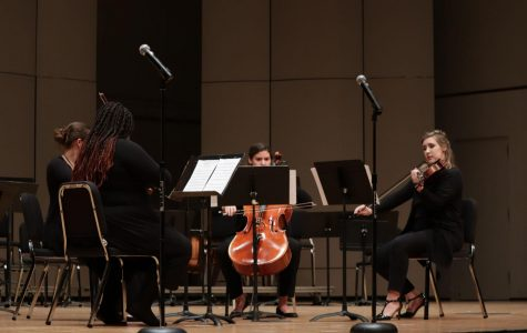 Poised and prepared: The quartet performs the written composition. They played in harmony on two violins, a viola and a cello.