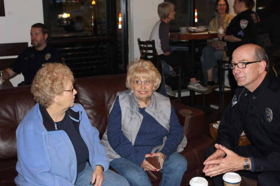 Daily dose: Topeka residents Bernice Tiekint and Darb Burgen chat with Topeka Police Department officer Koch. They enjoyed a cup of coffee and some cookies while they spoke.