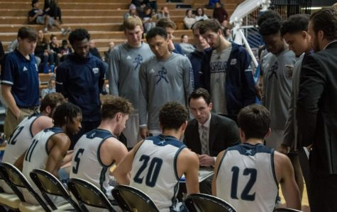 Timeout: The team intensely listening to their coach for advice on the next move of the game. The Men's Basketball team won Thursday's game by 10 points, 86-76.