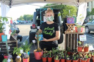 Ashley McDonald posing with her Glo Bowl stand where she sold plants and homemade pots. She and her family enjoyed coming to the Farmer's Market to sell their wares.