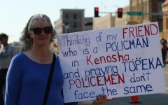 Community member Karen Pope holds a message at her side at TPAC to show support for local policemen.