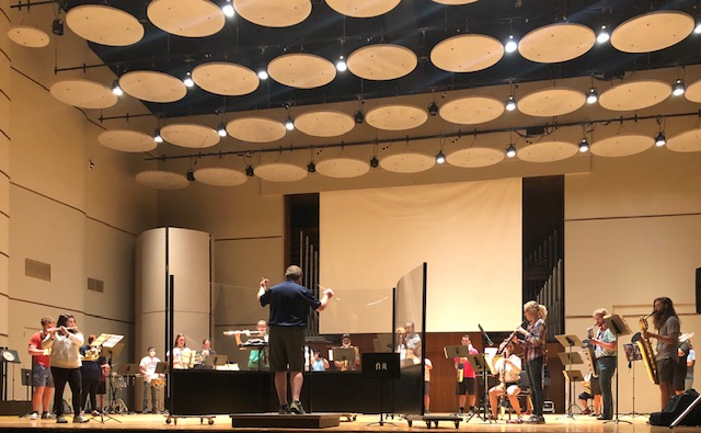 Band director and professor, Tom Seddon conducting an ensemble behind a plexyglass wall.