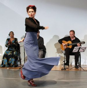 Swirling and Spinning: Melinda Hedgecorth performs a traditional Flamenco dance. Other members of the band play accompanying music or sing, adding to the spectacle.