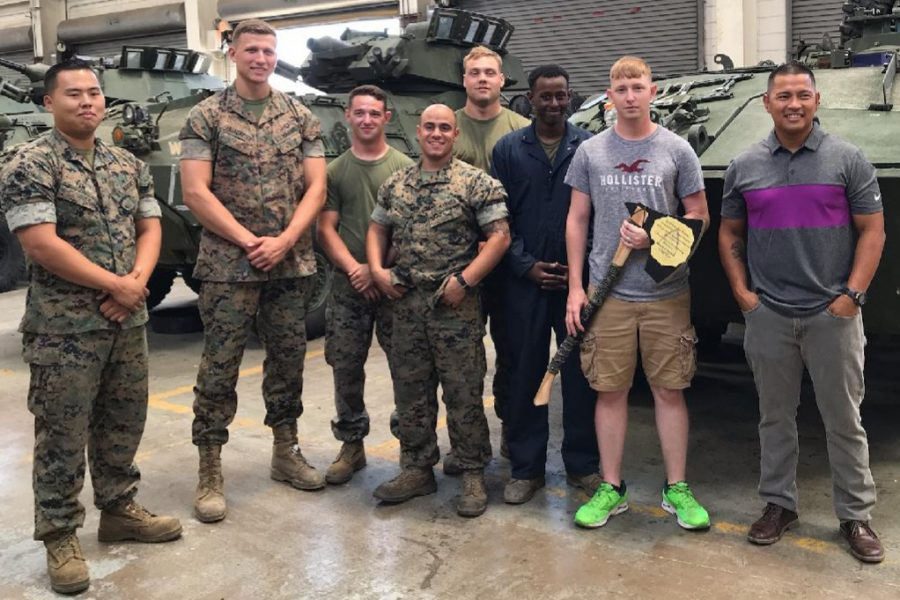 Fellow Marines present Andrew Kaufman with the axe during one of his last days with the unit.