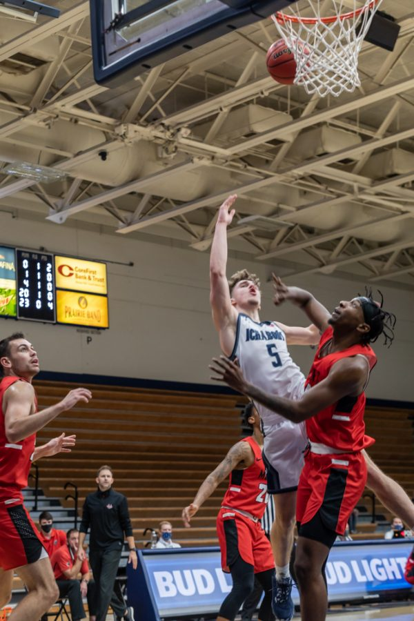 Taking the hit: Washburn's Senior guard Drew Maschoff driving in for two and getting fouled. Maschoff had a total of 14 points during Thursday night's game.