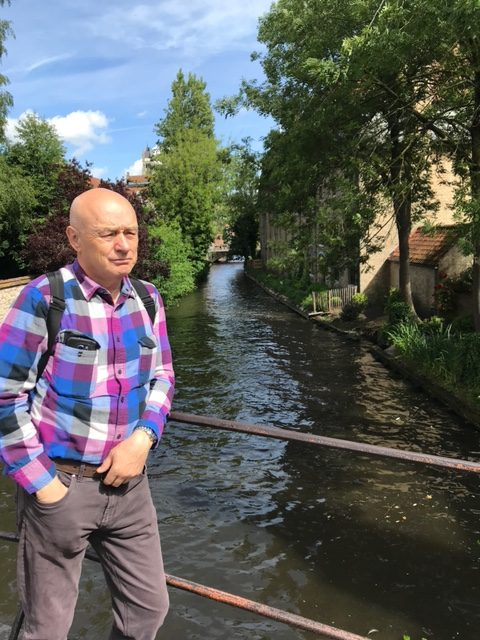 Perfect Scenery: Dr. Stoica posing in front of a canal in Bruges, Belgium. He enjoyed bringing his class to this beautiful location.